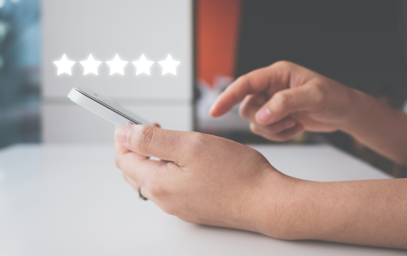 person submitting a 5 start review on their phone for a houston business